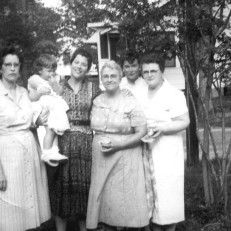 "Gulfport, Harrison, Mississippi, USA Bama Smith Grayson, Tenderly Rose Bosworth held by Janie Morris Bosworth, Rosie S. Morris, Patsy Grayson Gendron and Helen Hoagland Bosworth Mason standing together on front yard of ""Hungry Hill"" at 1711 Wisteria Street."