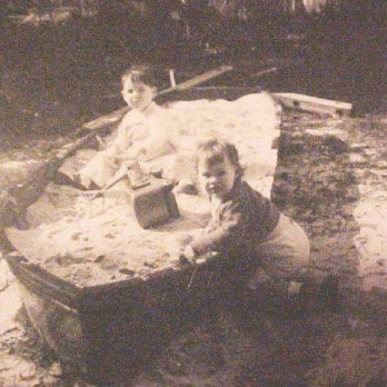cir 1957 Playing in an old fishing boat that belonged to Ed Morris, Kevin Cooper and Tenderly Rose enjoy the sand in the re-purposed john boat. The boat's final resting place was Rosie and John Morris's home at 1711 Wisteria Street in Gulfport, Mississippi (Gulf Gardens).